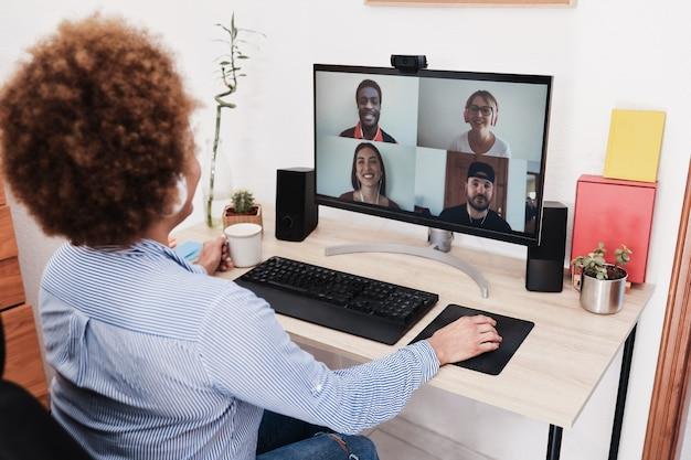 Afrikaanse vrouw met video-oproep met haar collega's met behulp van computer-app - soft focus op rechterhand