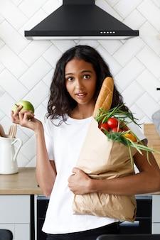 Afrikaanse vrouw staat op de keuken met een papieren zak met boodschappen en heeft verrast kijken