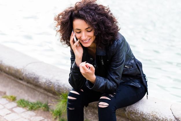 Afrikaanse vrouw telefoneren met mobiele telefoon bij stadsfontein