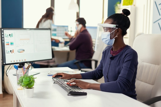 Afrikaanse vrouw typt op de computer op de werkplek en draagt een gezichtsmasker als veiligheidsmaatregel tegen covid19