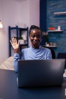 Afrikaanse vrouw zwaait naar de webcam van de laptop tijdens een videoconferentie die 's avonds laat werkt vanuit het thuiskantoor. zwarte freelancer die werkt met een team op afstand dat virtuele online conferentie chat.