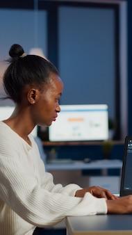 Afrikaanse vrouwelijke ingenieur die in een modern cad-programma werkt met uitrusting aan het bureau in een start-up bedrijfskantoor. industriële werknemer die prototype-idee bestudeert op laptop met cad-software op het scherm van het apparaat