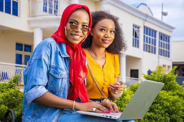 Afrikaanse vrouwen die online winkelen terwijl ze in een park zitten