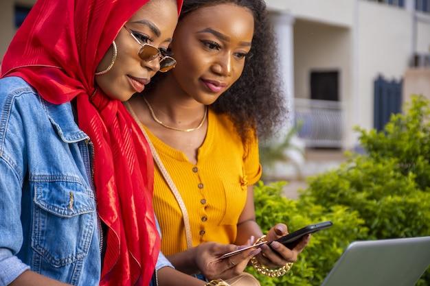 Afrikaanse vrouwen winkelen online terwijl ze in een park zitten