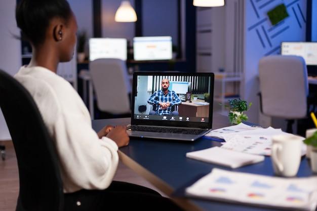 Afrikaanse werknemer die 's avonds laat overwerkt vanuit het bedrijfskantoor en online met partners praat via webcam