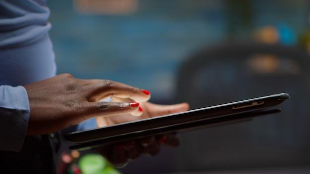 Afrikaanse werknemer die tablet gebruikt, zoekt, erop typt, 's avonds laat in de woonkamer staat en pauze neemt. zwarte freelancer die modern technologienetwerk draadloos gebruikt om overuren te lezen, te schrijven