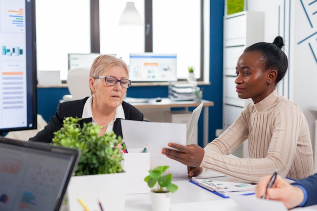 Afrikaanse werknemer in de vergaderruimte van het financiële zakenbestuur in gesprek met senior ondernemersinvesteerders die op zoek zijn naar het analyseren van projectdocumenten
