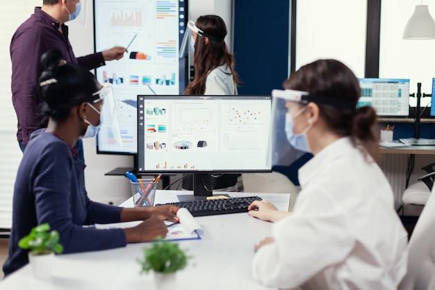 Afrikaanse werknemer luistert tijdens verkoopconferentie van trainer tijdens covid19. multi-etnisch team dat werkt in bedrijf met nieuwe norm met respect voor sociale afstand tijdens wereldwijde pandemie met coronavirus.