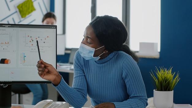 Afrikaanse werknemer met medisch gezichtsmasker die economisch project uitlegt aan verlamde invalide gehandicapte collega die de strategie van het bedrijf voorstelt