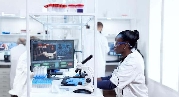 Afrikaanse wetenschapper die aan de computer werkt in een moderne faciliteit en collega's op de achtergrond. zwarte gezondheidszorgonderzoeker in biochemisch laboratorium die steriele apparatuur draagt.