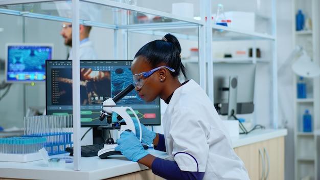 Afrikaanse wetenschapper die een monster van het virus controleert met behulp van een microscoop in een modern laboratorium. multi-etnisch team dat de evolutie van vaccins onderzoekt met behulp van hightech voor wetenschappelijk onderzoek naar de ontwikkeling van behandelingen tegen covid19