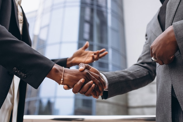 Afrikaanse zakelijke mannelijke mensen die handen schudden