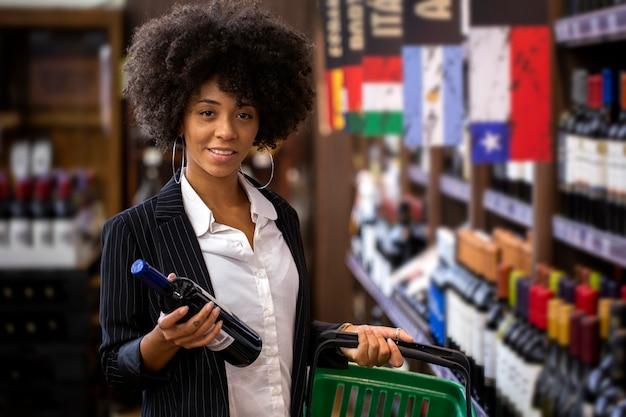 Afrikaanse zaken vrouw met flessen wijn in de supermarkt.