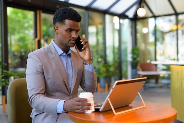 Afrikaanse zakenman bij coffeeshop die laptopcomputer gebruikt terwijl hij aan de telefoon praat