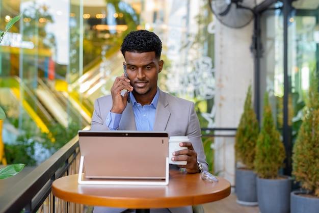 Afrikaanse zakenman bij coffeeshop met behulp van laptopcomputer en praten over de telefoon