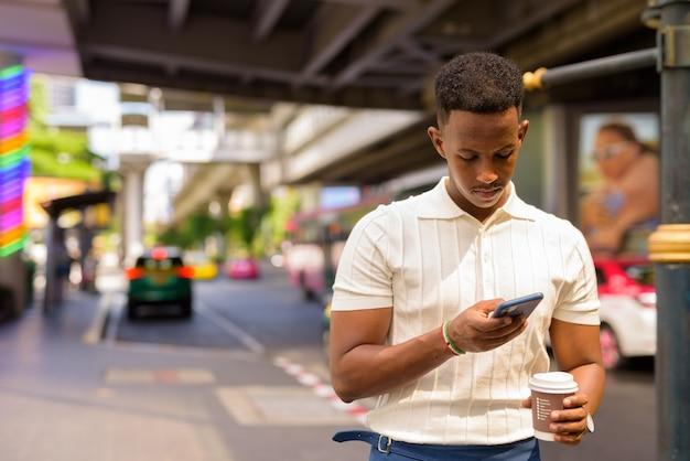 Afrikaanse zakenman die vrijetijdskleding draagt terwijl hij een mobiele telefoon gebruikt en een koffiekopje vasthoudt op het taxistation in de stad