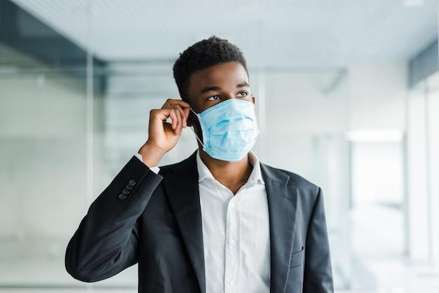 Afrikaanse zakenman draagt een mondbescherming om te voorkomen dat hij ziek wordt op het werk op kantoor