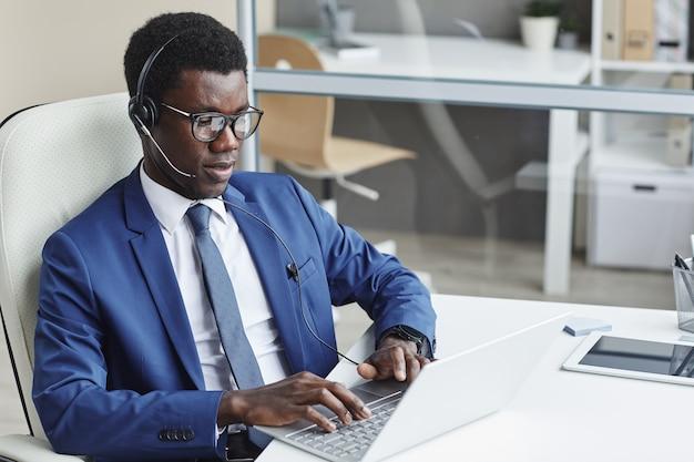 Afrikaanse zakenman hoofdtelefoon typen op toetsenbord van de computer op zijn werkplek op kantoor