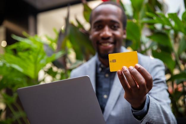 Afrikaanse zakenman houdt een creditcard vast en doet een online aankoop met zijn laptop