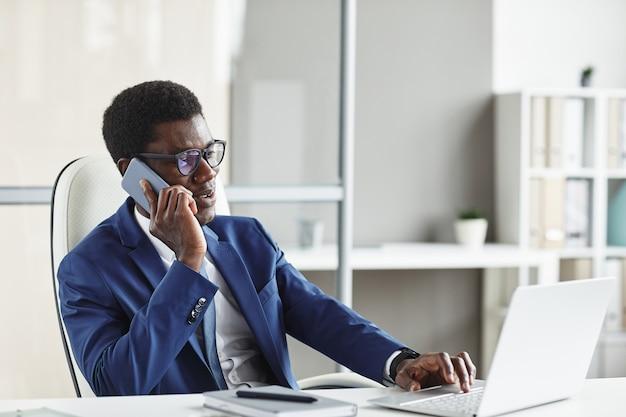Afrikaanse zakenman in bril doet zijn werk op laptopcomputer tijdens het gesprek aan de telefoon op zijn werkplek op kantoor