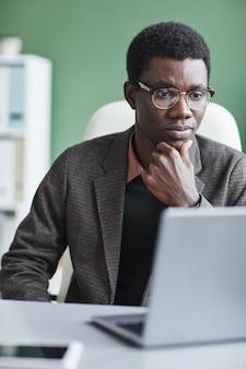 Afrikaanse zakenman in brillen monitor van laptop kijken en online werken aan de tafel