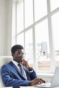 Afrikaanse zakenman in brillen typen op laptopcomputer zittend aan de tafel op kantoor