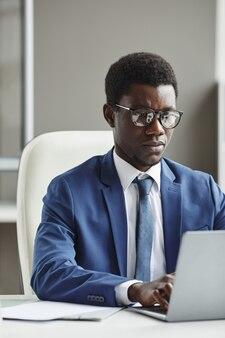 Afrikaanse zakenman in formalwear die zich op zijn online werk concentreert die hij aan de tafel zit te typen op laptop