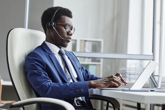 Afrikaanse zakenman in koptelefoon typen op laptopcomputer op zijn werkplek hij werkt in callcenter
