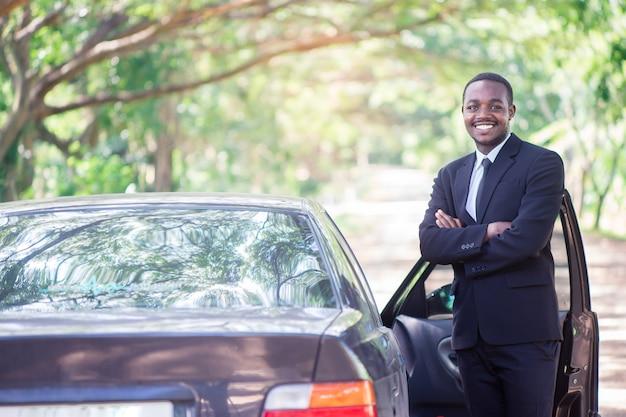 Afrikaanse zakenman in pak staande in de buurt van de auto met groene natuurlijke achtergrond.