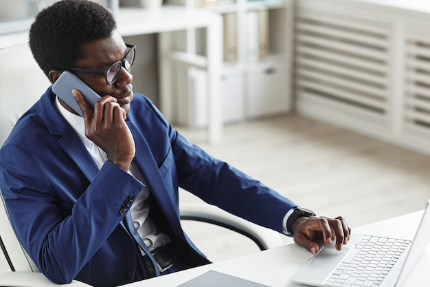 Afrikaanse zakenman in pak zittend op zijn werkplek computertoetsenbord te typen en te praten op de mobiele telefoon op kantoor