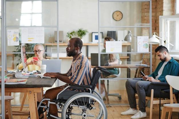 Afrikaanse zakenman in rolstoel zittend aan tafel voor computermonitor en werken met zijn collega's bezig met werk op de achtergrond