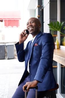 Afrikaanse zakenman met een zak die op mobiele telefoon spreekt
