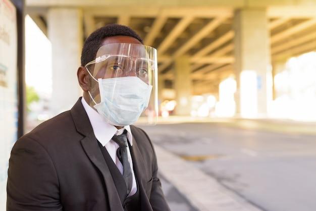 Afrikaanse zakenman met masker en gezichtsschild die bij de bushalte in openlucht in de stad wachten