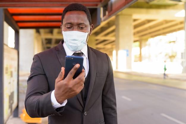 Afrikaanse zakenman met masker met behulp van telefoon tijdens het wachten bij de bushalte