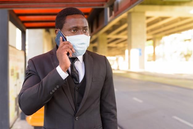 Afrikaanse zakenman met masker praten aan de telefoon tijdens het wachten bij de bushalte