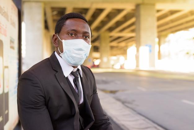 Afrikaanse zakenman met masker zitten en wachten bij de bushalte