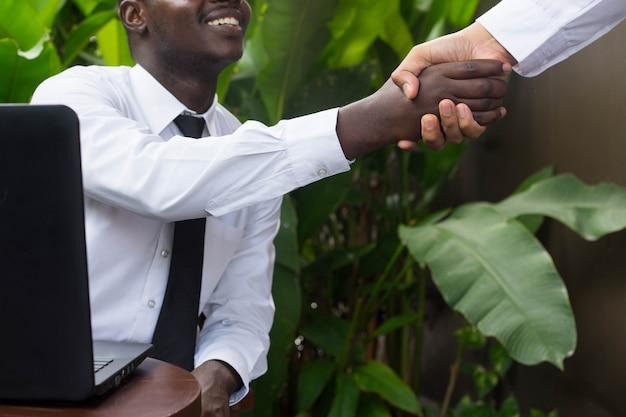 Afrikaanse zakenman schudden handen aan aziatische man.