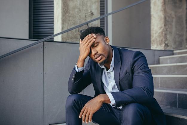 Afrikaanse zakenman zit gefrustreerd op de trap, depressief door de resultaten van zijn werk, hand in hand achter zijn hoofd