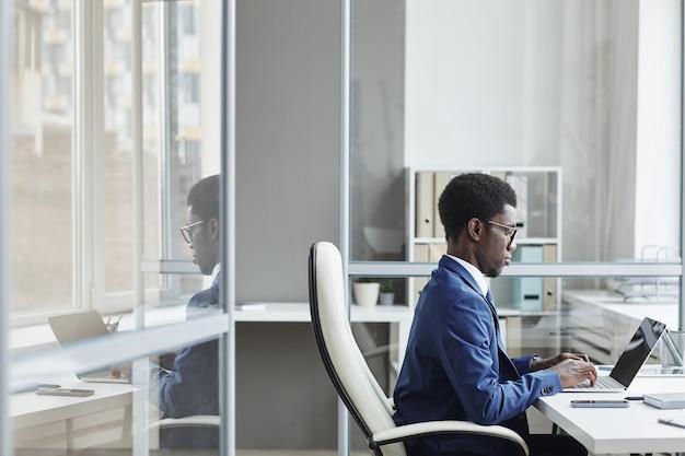 Afrikaanse zakenman zit op zijn werkplek te typen op laptop hij online werkt op kantoor