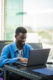 Afrikaanse zakenman zittend aan tafel in café werken met laptop en papieren en koffie drinken