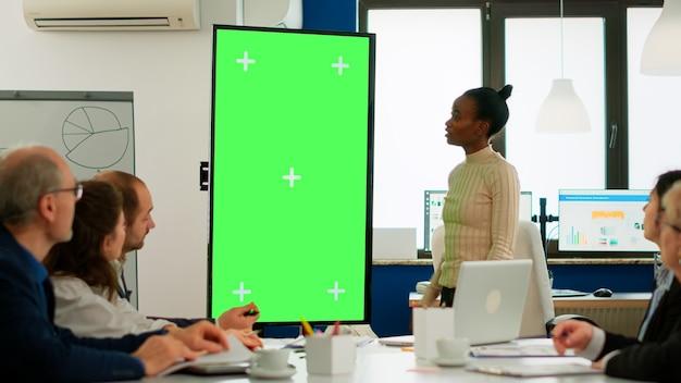 Afrikaanse zakenvrouw die jaarlijkse financiële rapporten analyseert die in de vergaderruimte staan, wijzend op een groen schermmonitor. leider legt projectstrategie uit met behulp van greenscreen-pc met chroma key-display