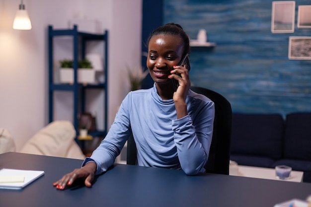 Afrikaanse zakenvrouw die op smartphone spreekt en 's avonds laat werkt vanuit kantoor aan huis. drukke gerichte freelancer met behulp van moderne technologienetwerken die overuren maken.