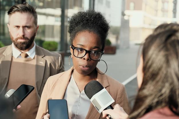 Afrikaanse zakenvrouw die op straat wordt geïnterviewd, spreekt ze met journalisten