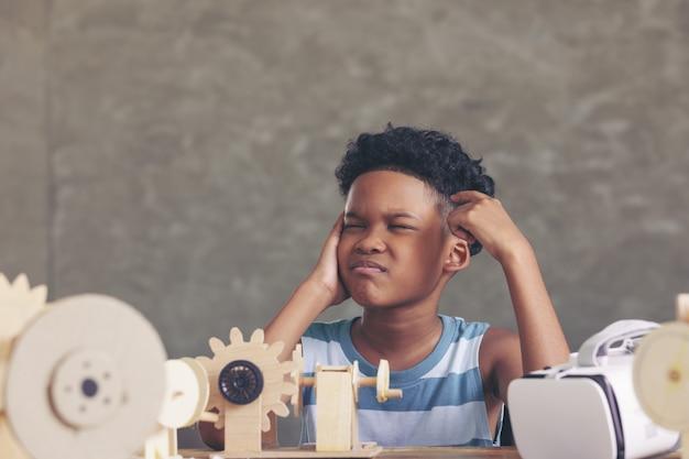 Afrikaanse zwarte jongen die denkt na te denken over het ontwerp van het simulatiemechanisme robotmodel houten