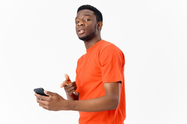 Afro-amerikaan met een mobiele telefoon en in een oranje t-shirt op een lichte achtergrond