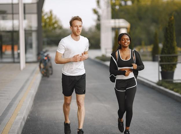 Afro-amerikaans fitnessmodel en blanke man die buiten jogt