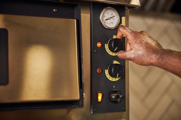 Afro-amerikaans fornuis dat bakapparatuur aanzet voor het bereiden van pizza