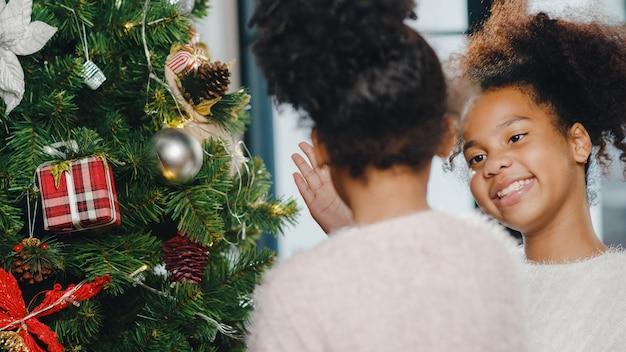 Afro-amerikaans kind versierd met ornament op kerstboom