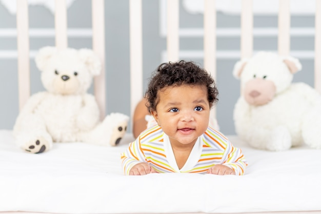 Afro-amerikaans klein kind liggend in bed in oranje kleren met zachte beren
