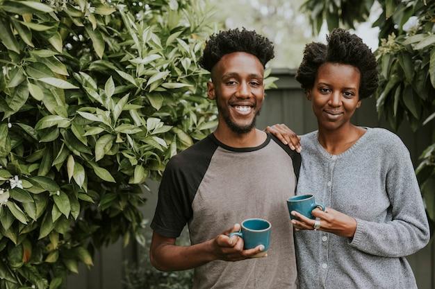 Afro-amerikaans koppel met koffie in de tuin